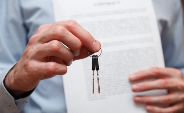 Man sieht eine Person, die einen Vertrag und ein Paar Autoschlüssel in der Hand hält
